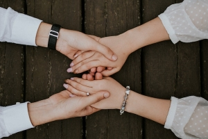 Zwei Menschen halten sich an den Händen.