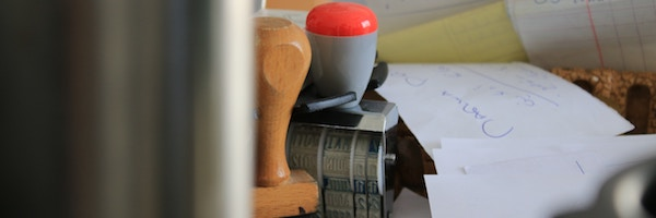 Verschiedene Stempel und Arbeitszettel liegen auf einem Tisch.