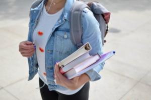 Eine Schülerin hält Bücher in ihrem Arm.