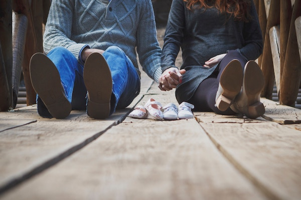 Ein werdendes Elternpaar hält sich an der Hand.