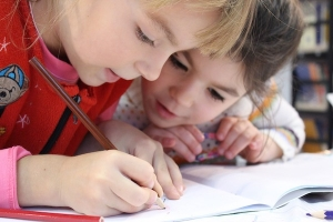 Kinder schreiben zusammen in ein Buch.
