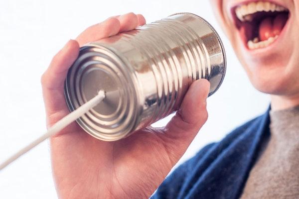 Ein Mann spricht in ein Dosentelefon.