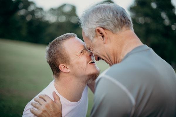 Menschen mit verschiedenen Beeinträchtigungen umarmen sich lachend.