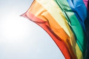 Eine Regenbogenflagge weht im Wind.