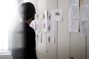 Ein junger Mann informiert sich an einer Pinnwand.