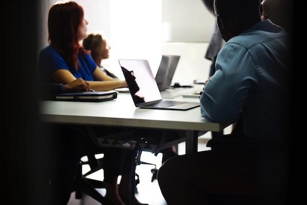 Menschen sitzen in einem Kursraum an ihren Computern.