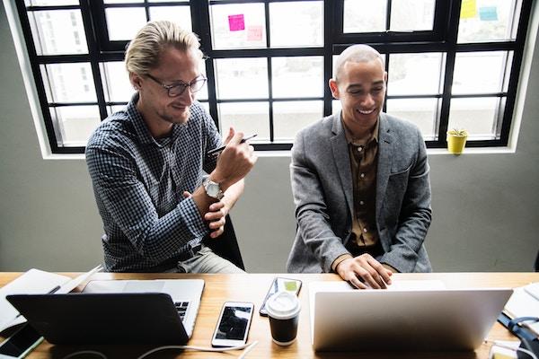Zwei Männer sitzen an einem Tisch und arbeiten zusammen.