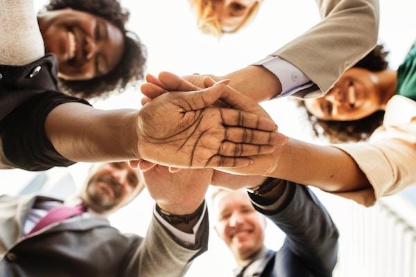 Verschiedene Menschen legen ihre Hände zusammen.