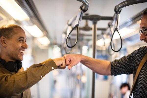 Zwei Männer begrüßen sich lachend.